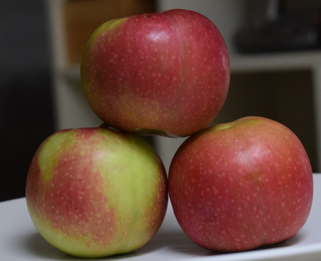 Three McIntosh Apples stacked.